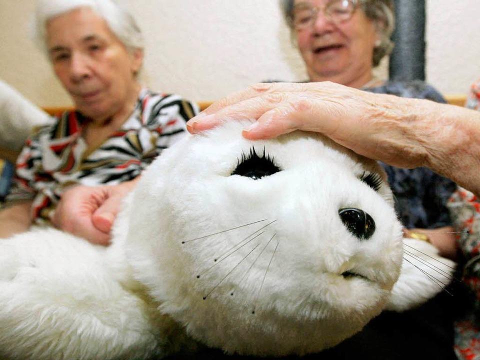 "Paro verbindet: ""Wenn er da ist,...n"", sagt Therapeutin Wilma Falk.  | Foto: dpa"