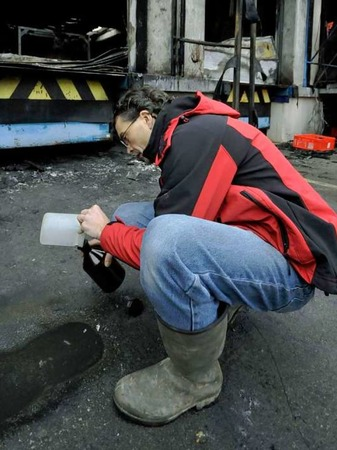 Ein Mitarbeiter  des Umweltschutzamtes Freiburg nimmt eine Probe aus einer Pf�tze L�schwasser.