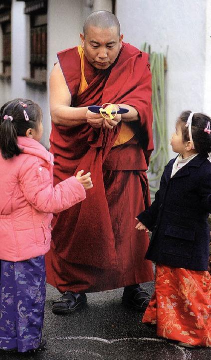 Geshe Gedun Shayka spielt mit zwei jungen Besucherinnen.    Foto: Bildband