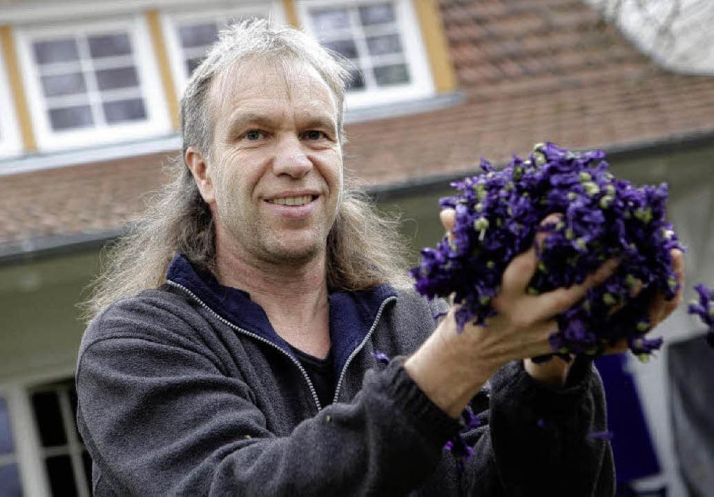 Zeigt her eure Kräuter: Rudi Beiser mit einer Handvoll violetter Blüten    Foto: Christoph Breithaupt