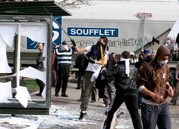 Demonstranten zerstören ein Buswartehäuschen.