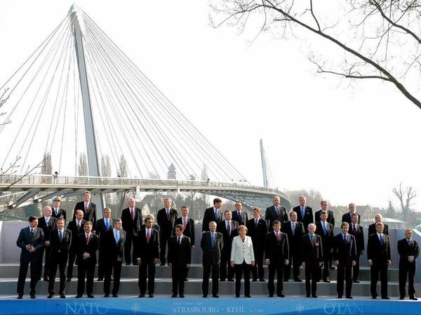 """Im Hintergrund die """"Br�cker der zwei Ufer"""", im Vordergrund die Regierungschefs der Nato-Mitglieder."""