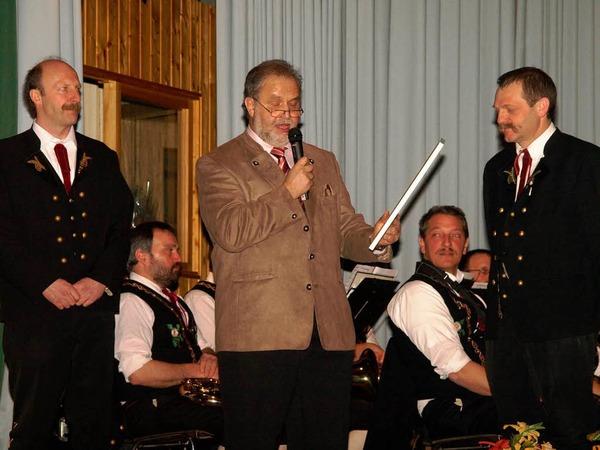 Vorstand Thomas Schmid und Verbandspräsident Franz Bayer (von links) bei der Ehrung von Dirigent Thomas Villinger mit der Goldenen Ehrennadel für 40-jährige aktive Tätigkeit in der Blasmusik