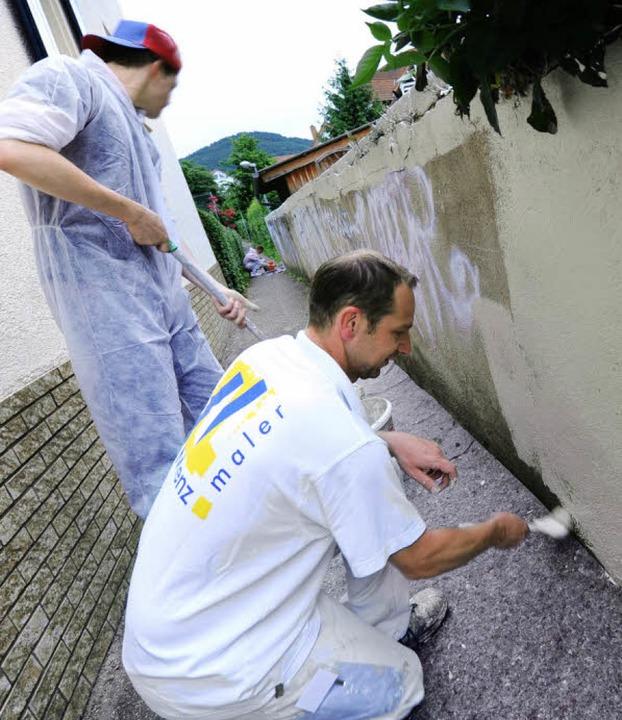 Maler Rüdiger Steigert (vorne) entfern...n,  Graffiti entlang der Ochsengasse.     Foto: Rita Eggstein