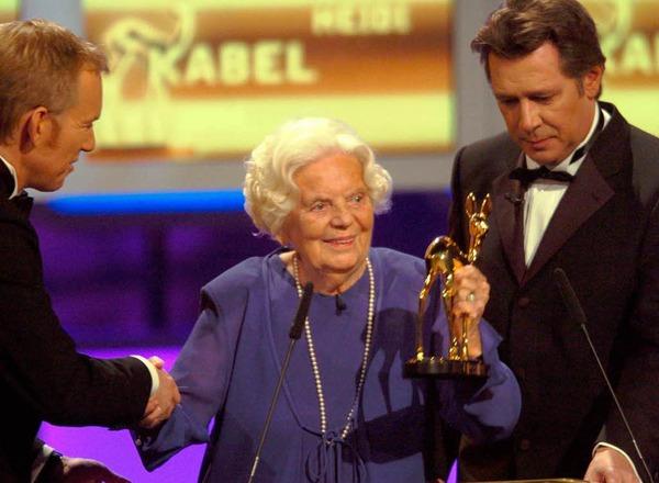 2004: Der Moderator Johannes B. Kerner (l) überreicht der Schauspielerin Heidi Kabel bei der 56. Bambi-Verleihung in Hamburg neben ihrem Laudator Jan Fedder (r) das goldene Rehkitz