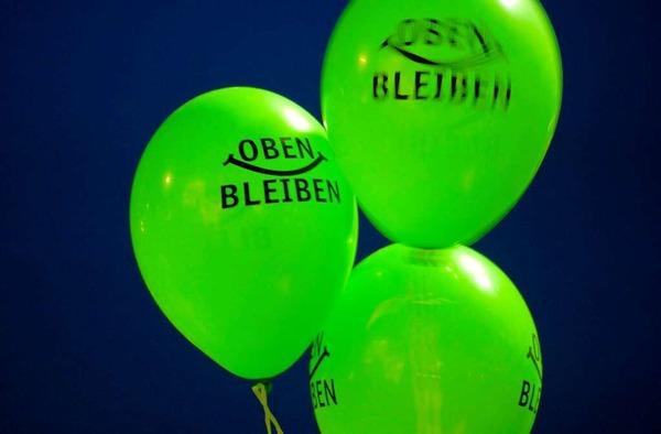 """Luftballons mit der Aufschrift """"Oben bleiben"""" werden am Freitagabend in Stuttgart während einer Kundgebung auf dem Schlossplatz hochgehalten."""
