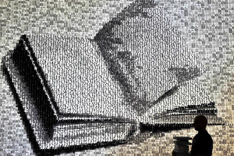 Ein riesiges Buch wurde aus mehreren tausend kleiner Porträtfotos zusammengestellt. (Foto: dpa)