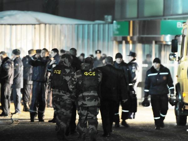 Sprengstoffexperten des russischen Inlandsgeheimdienstes FSB und Polizisten stehen vor dem Flughafen Domodedowo in Moskau.