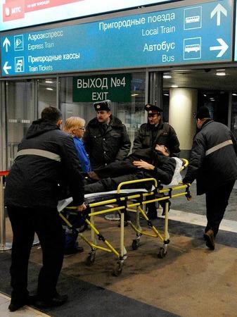 Sanit�ter schieben im Flughafen Domodedowo in Moskau einen Verletzten auf einer Trage.