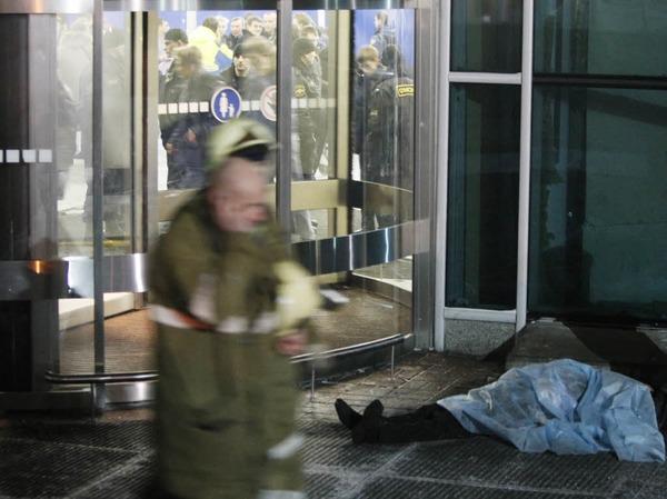 Vor einer Eingangstür des Flughafengebäudes liegt eine Leiche.