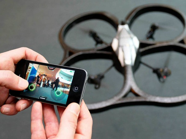Mittels eines iPhones steuert ein Mitarbeiter einen Quadcopter.