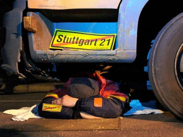 Ein Gegner des Bahnprojekts Stuttgart 21 blockiert  in Stuttgart am Nordflügel des Hauptbahnhofs ein Baufahrzeug.