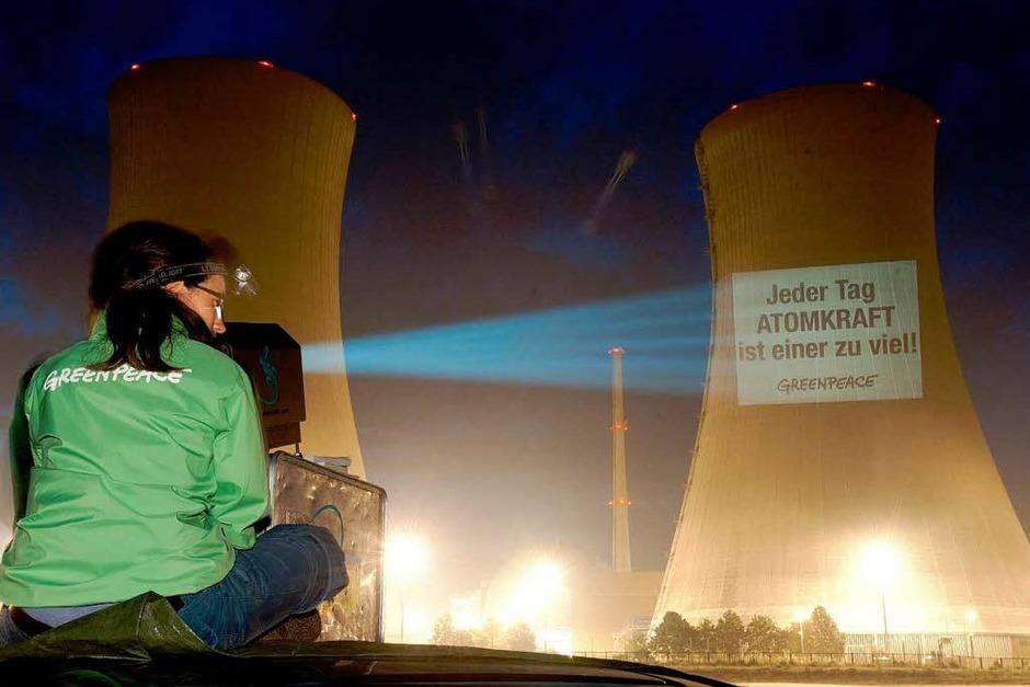 Zeitgleich projizieren die Aktivisten  ihre Forderungen an die AKWs. (Foto: dapd)