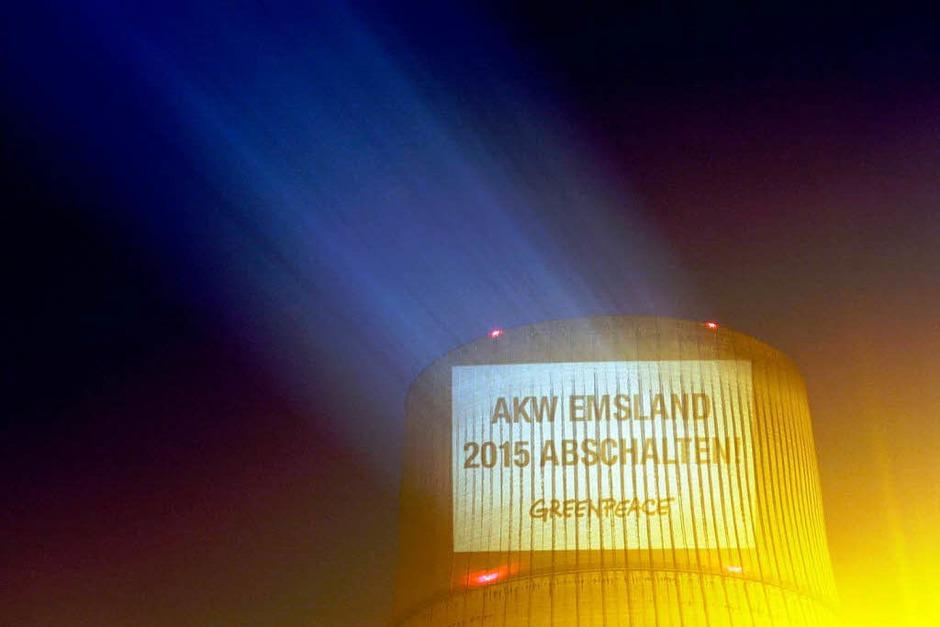 Greenpeace-Aktivisten projizieren das eingeforderte Abschaltdatum an Kühltürme. (Foto: dapd)