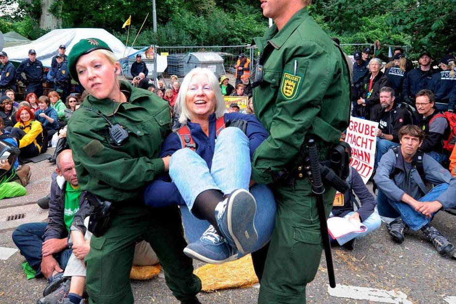 Die Polizei trägt eine Stuttgart-21-Gegnerin vor einem Bautor weg. (Foto: dpa)