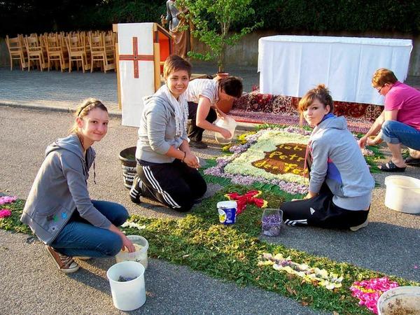 Auch die Firmlinge halfen beim Legen der Blumenteppiche.
