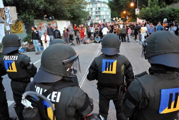 De dos, des agents antiémeutes avec des masques à bonbonne d'oxygène et tout leur armure, devant, une foule de gens aux diverses apparences et âges, le tout sur une rue vue un peu de haut.