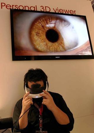 Mit einer Spezialbrille testet ein Journalist eine 3D-Vorführung.