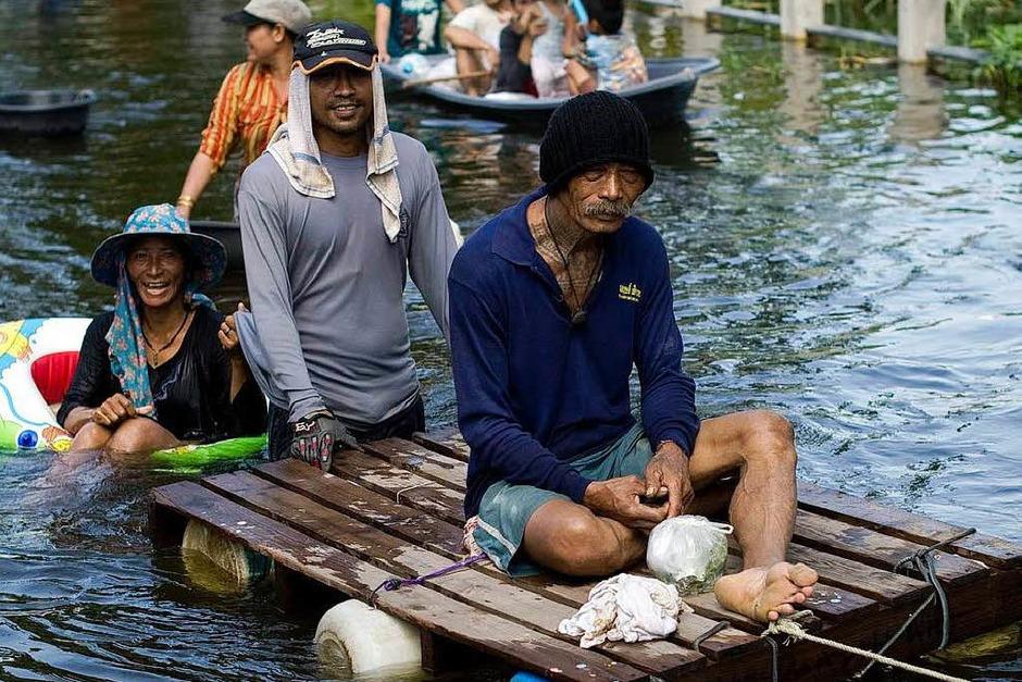Thailands Hauptstadt Bangkok steht unter Wasser. Millionen Menschen sind betroffen – und haben Wege finden müssen, trocken zu bleiben. (Foto: AFP)
