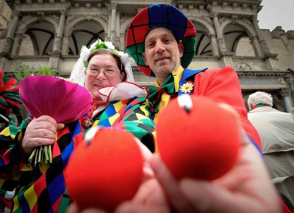 Das Brautpaar Rita Noak (l.) und Frank Awalda in Köln vor dem Standesamt mit ihren Eheringen, die in roten Pappnasen stecken.