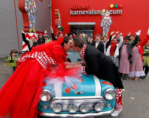 Daniel Greve und seine frisch angetraute Frau Kerstin (l.) küssen sich in Köln nach ihrer Trauung vor dem Karnevalsmuseum.