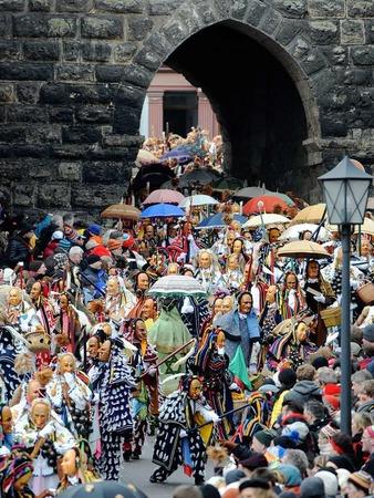 Federahannes, Biß und Gschell, die Rottweiler Narrenfiguren, laufen in Rottweil durch das Schwarze Tor.