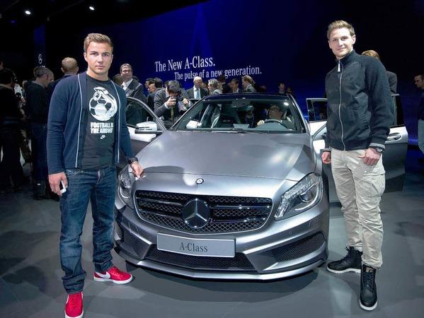 Die Nationalspieler Benedikt Hoewedes (r.) und Mario Goetze posierenin Genf beim Autosalon vor der neuen Mercedes-Benz A-Klasse.