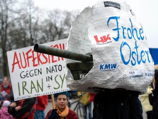 """Ein Demonstrant tr�gt am Samstag in M�nchen w�hrend eines Ostermarsches ein stilisiertes Osterei mit der Aufschrift """"Frohe Ostern"""", aus dem ein Panzer gefahren kommt, auf dem Kopf."""