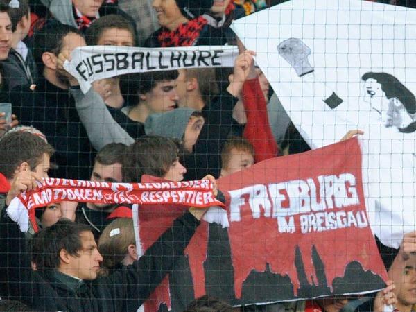 Blick auf die Ränge, Teil I: Freiburger Anhänger mit gedruckten Unfreundlichkeiten.
