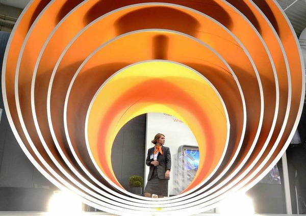 Eine Frau steht auf dem Messegelände in Hannover hinter Stahlröhren auf dem Messtand der Salzgitter AG.