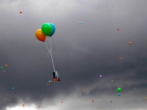 An den Luftballons hängen Karten...