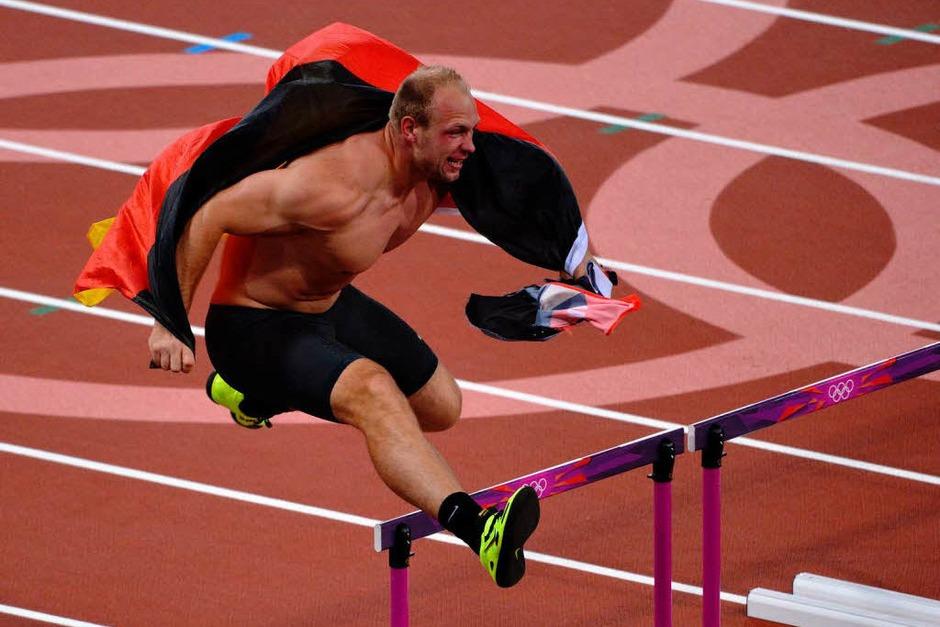 Olympiasieger! Nach seinem Goldwurf dreht Diskuswerfer Robert Harting eine Ehrenrunde im Stadion. Die Hindernisse des 100-Meter-Hürdenlaufs nimmt er gekonnt mit. (Foto: AFP)