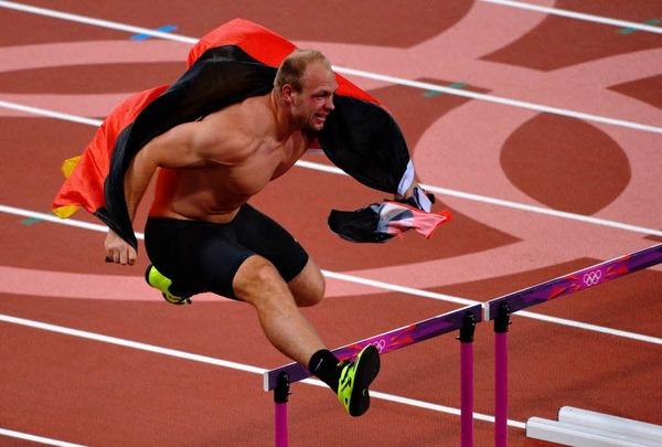 Olympiasieger! Nach seinem Goldwurf dreht Diskuswerfer Robert Harting eine Ehrenrunde im Stadion. Die Hindernisse des 100-Meter-Hürdenlaufs nimmt er gekonnt mit.