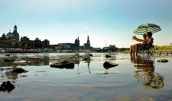 In Dresden kühlen sich am Sonntag zwei junge Männer die Füße in der Elbe, gegenüber der Altstadt.