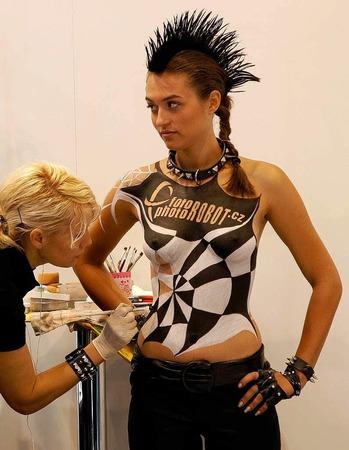 Model am Stand der Firma Photo Robot wird für ihren Auftritt bemalt.