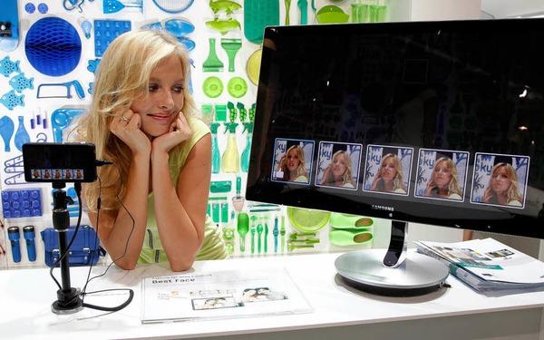 Model posiert am Stand der Firma Samsung für eine Kamera der Galaxy-Serie.
