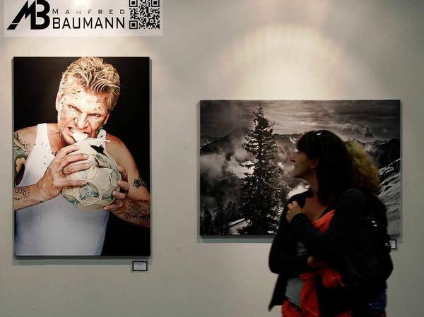 Besucher vor Bildern des Fotografen Manfred Baumann