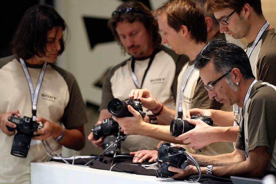 Mitarbeiter von Sony machen sich mit neuen Digitalkameras vertraut. (Foto: dpa)