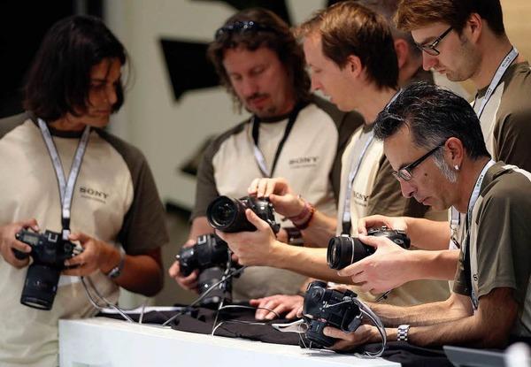 Mitarbeiter von Sony machen sich mit neuen Digitalkameras vertraut.