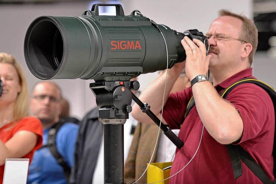 Ein Mann schaut durch ein Riesen-Teleobjektiv. (Foto: dapd)