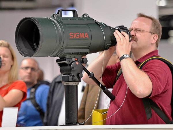 Ein Mann schaut durch ein Riesen-Teleobjektiv.