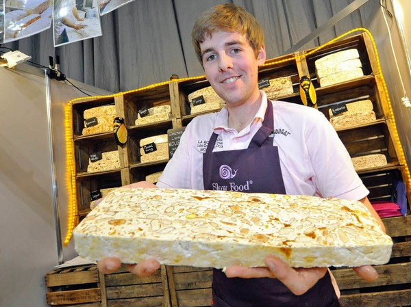 """Was Andrew Williamson hier in die Kamera hält, ist keine marmorierte Steinplatte sondern butterweiches weißes Nougat aus der Provence. Eine Süßigkeit aus Eiweiß, Zucker, Pistazien und, besonders wichtig, Lavendelhonig. """"Man hat das Gefühl, man beißt in die Provence"""", sagt Williamsons Kollegin. Auszuprobieren am Slow-Food-Stand in Halle zwei."""