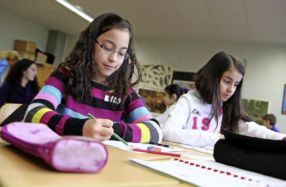 Schülerinnen beim Malen von Buchstaben   | Foto: Christoph Breithaupt