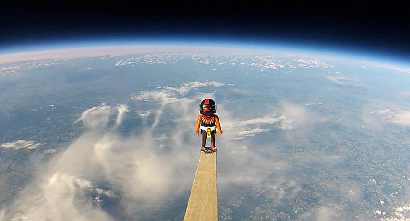 Ein Playmobil-Mann fliegt an einem Ballon über  Schweizer Wolken.   | Foto: Speerli