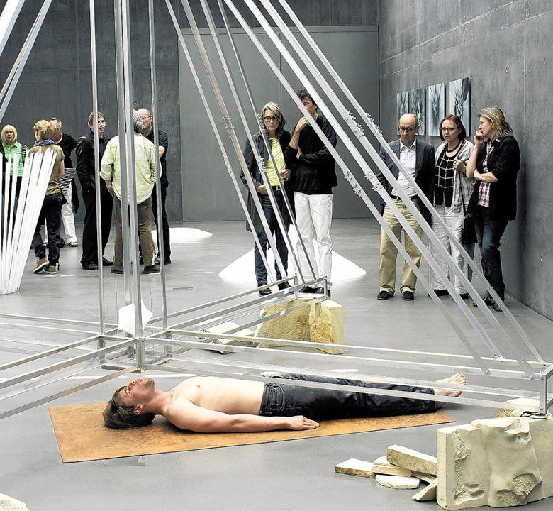 Szenen einer Ausstellung: Simon Pfeffe... Putze zertritt jede Menge Bierdosen.     Foto: Fischer