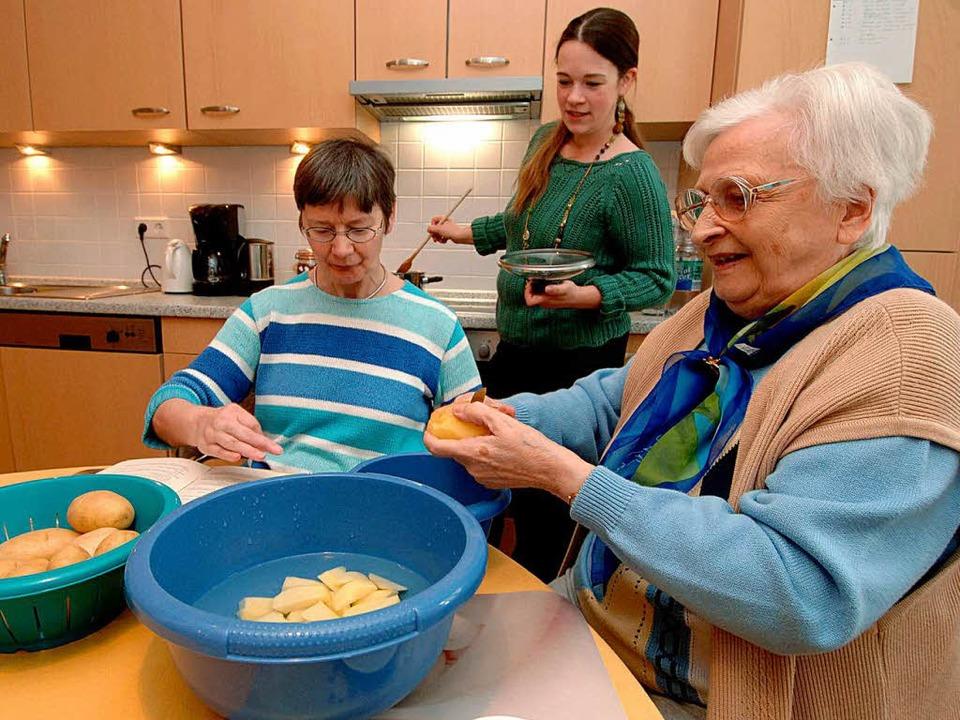 Senioren kochen gemeinsam mit einer He...ner Wohngemeinschaft ihr Mittagessen.     Foto: DPA