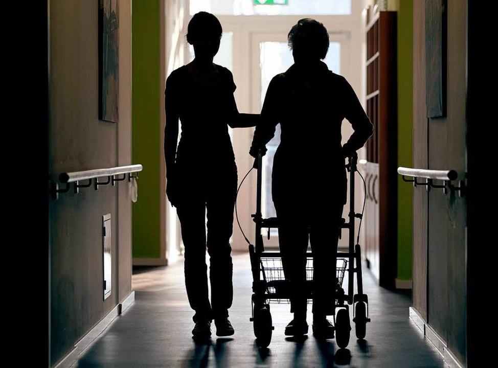 Eine Pflegerin begleitet eine Frau mit Rollator.   | Foto: DPA