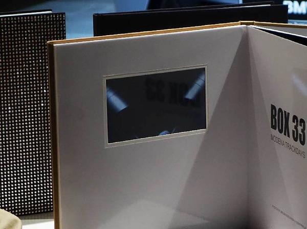 Fujifilm bietet nicht nur das Swarovski-Fotobuch (im Hintergrund), sondern auch eines mit integrierter Video-Abspielmöglichkeit
