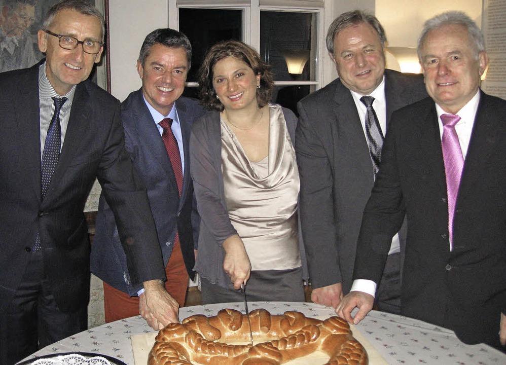 Anschnitt der Neujahrsbrezel: Armin Sc...udrack und Ottmar Seywald (von links).    Foto: Privat