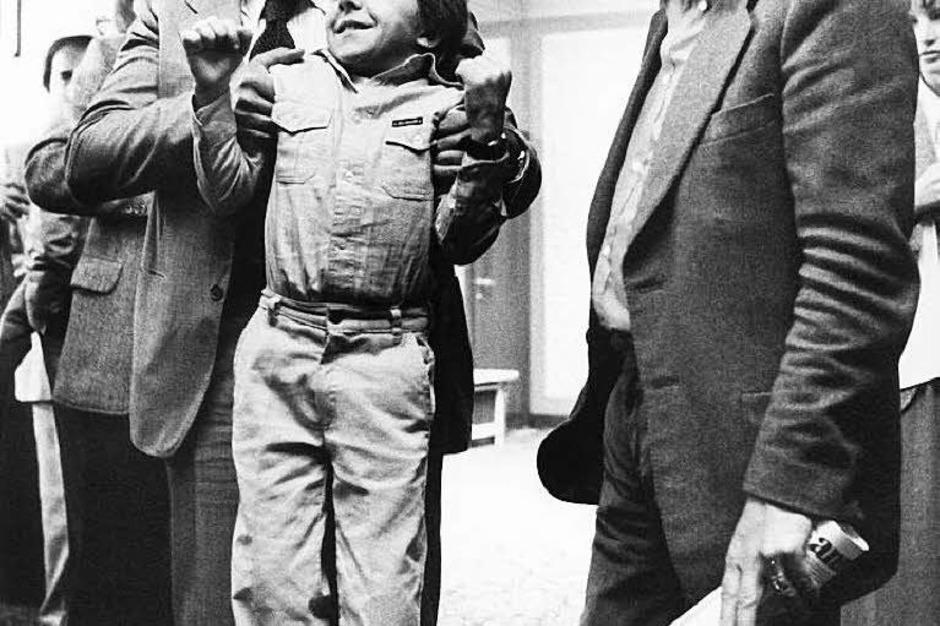 """David Bennent, der 12-jährige Hauptdarsteller, wird auf der Pressekonferenz vor der Uraufführung des Films """"Die Blechtrommel"""" am 03.05.1979 in Berlin von seinem Filmvater Mario Adorf hochgehoben. Rechts der Autor der Romanvorlage, (Foto: dpa)"""